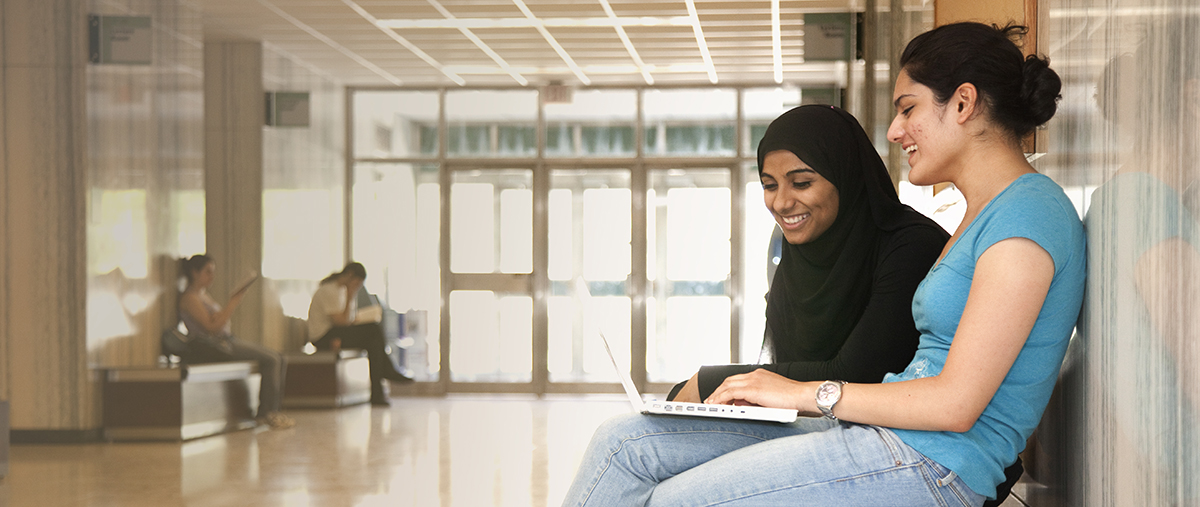 Two students sitting in hallway and looking at laptop screen
