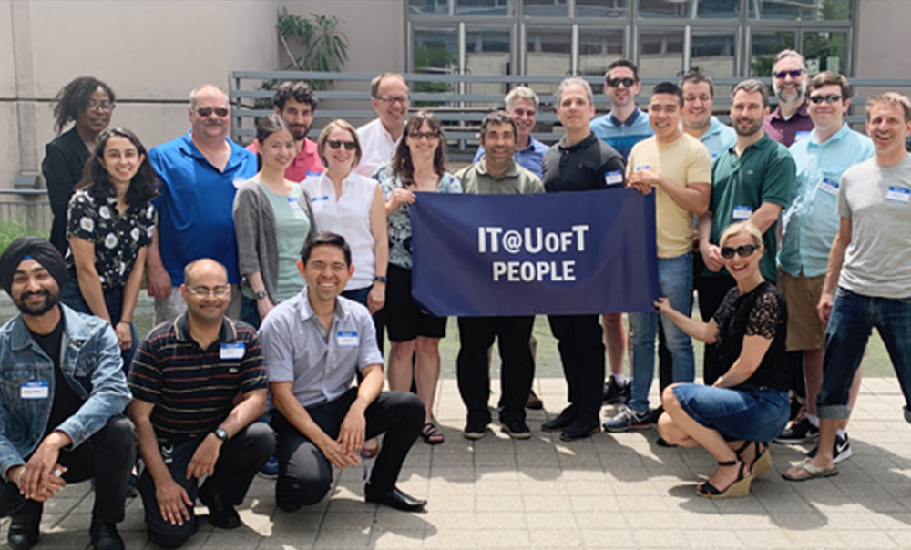 """EASI's Digital Workplace team holding """"IT@UofT People"""" banner outdoors"""
