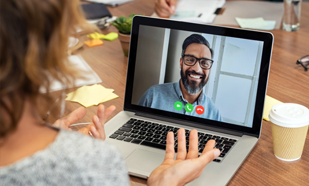 Woman talking to man on computer screen during video meeting