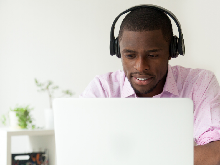 Man with headphones working on a laptop