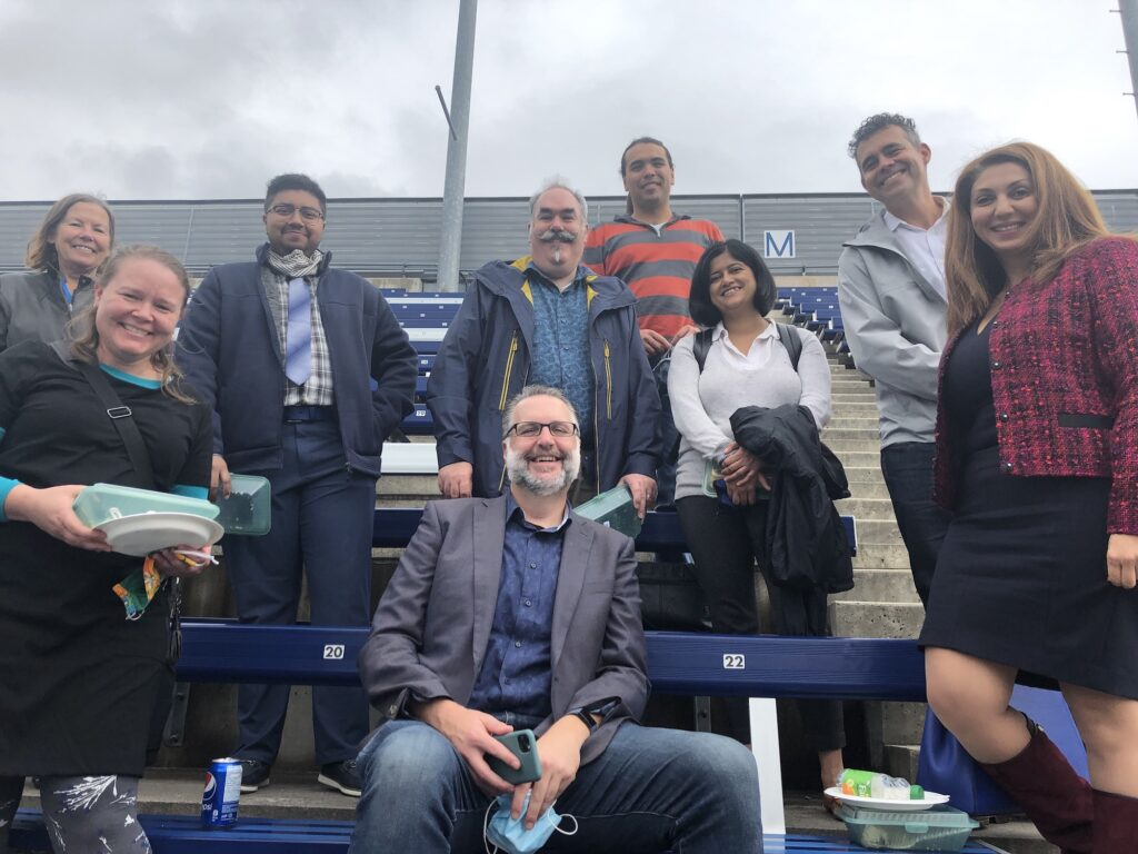 Nine Information Security staff members on the bleachers at the OREP awards ceremony.