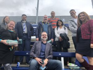 A photo of nine ITS staff members sitting and standing on the bleachers at the OREP event.